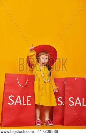 Kid's fashion. Emotional lovely little girl in bright yellow dress and a red hat stands with shopping bags, raises her index finger up and wonders. Yellow background with copy space.