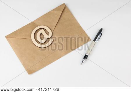 An envelope with pen and wood sign E-mail lies on a white background. Concept e-mail message letter. Top view