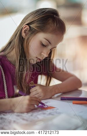 Little School Girl Painting at Home. Draws in Coloring Book. Home Education. Self Isolation. Enjoying Leisure Time. School, Art and Hobby Concept