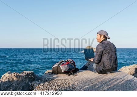 Traveler Man Sitting In Front Of The Sea Using His Laptop And Thinking About His Future Trip. Nomadi