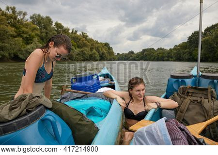 Girls, canoeing, swimming in the river, climbing back into the canoe