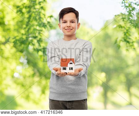 mortgage, real estate and accommodation concept - smiling boy holding house model over green natural background