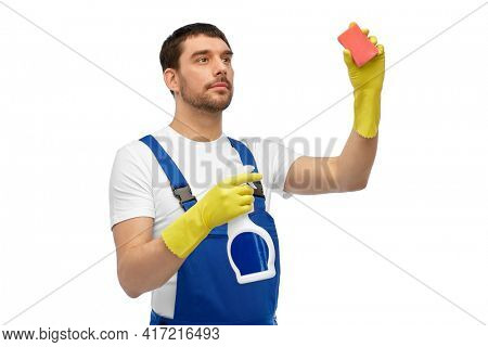 profession, cleaning service and people concept - male worker or cleaner in overall and gloves with sponge and detergent over white background