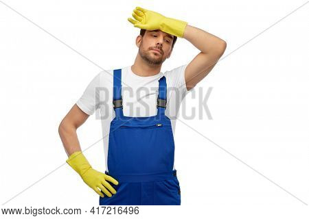 profession, cleaning service and people concept - tired male worker or cleaner in overall and gloves over white background