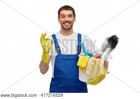 profession, service and people concept - happy smiling male worker or cleaner in overall and gloves with cleaning supplies showing ok hand sign over white background