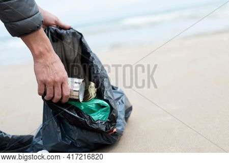 a young caucasian man collects some waste, such as cans, bottles or plastic bags, from the sand of a lonely beach, as an action to clean up the natural environment