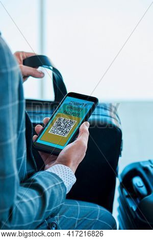 a young caucasian businessman, wearing an elegant gray suit, has a simulated electronic covid-19 immunity passport in his smartphone, sitting in the waiting hall of an airport