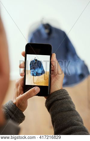 a young caucasian man takes a picture, with his smartphone, of a shirt to sell it on an online marketplace app to sell and buy secondhand goods