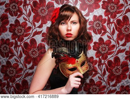 Young brunette woman with long curly hair with masquerade mask.