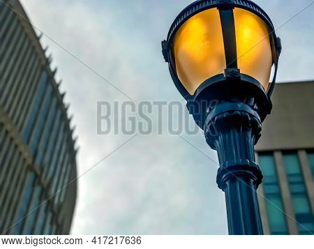 Street Light Lamp On Pole Against A Blurry Background, From A Low Angle View. The Focus Is On The Li