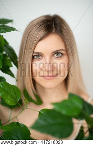Beautiful calm middle aged woman with green plant, natural light. Anti-aging and beauty treatment.