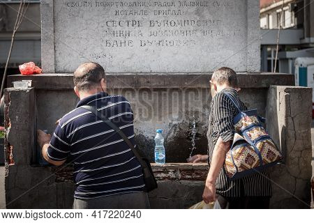 Belgrade, Serbia - June 8, 2019: Two Men Filling Bottles And Drinking Water At A Public Drinking Fou