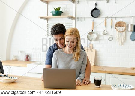 The Caucasian Family Use A Laptop Computer To Shop Online At Home. The Husband And Wife Are Happy To