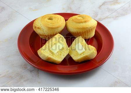 Corn Swirl Muffins With Butter Pats On Halves On Red Bread Plate