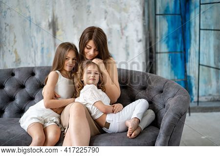 Mom On The Couch Cuddles With Her Daughters. Happy Family.