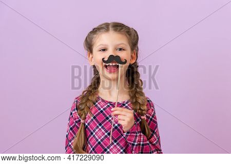 The Child Holds A Masquerade Black Moustache Near His Face.