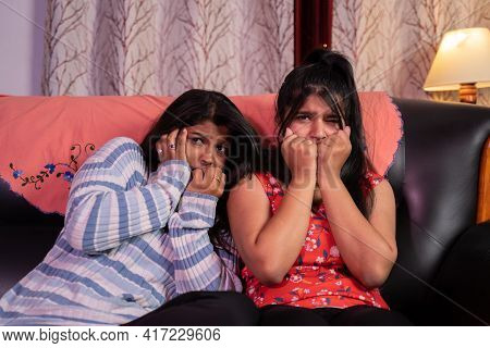 Two Scared Girls Watching Horror Movie Or Cinema While Sitting On Sofa At Home.