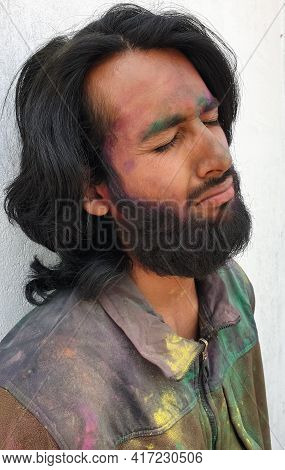 Side View Of Handsome Young Man Covered With Multi Color Holi Powder With White Wall Background, Bea