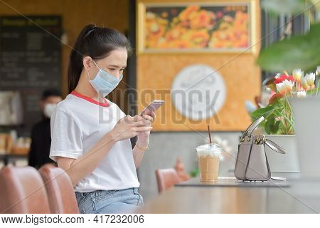 Asian Women Wear Surgical Mask And Using Smartphone In Cafe ,women Wear Medical Mask Protect Coronav