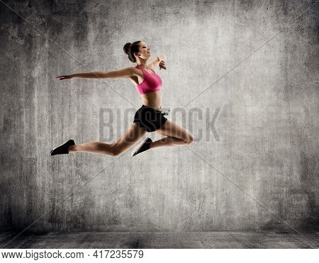 Woman Jumping Sport Dance. Young Happy Fit Girl Flying In Jump. Gymnastics Fitness Exercise Over Gru