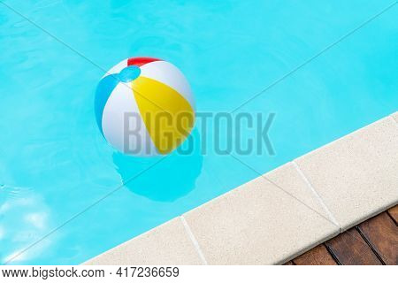 Colorful Beach Ball Floating On A Swimming Pool. Copy Space