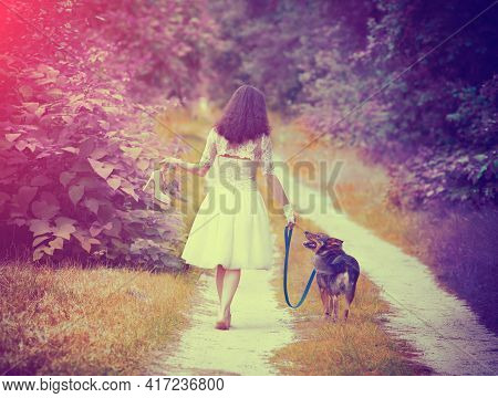 Young Bride Wearing Wedding Dress Walking Barefoot With Dog On Rural Road Back To Camera. Woman Brin