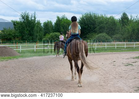 Young Caucasian Woman On Horse Back In Countryside. Horseback Riding As Hobby In Paddock On Woods. G