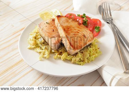 Tuna Steaks On Creamy Savoy Cabbage With Tomatoes, Lemon Slices And Parsley Garnish On A White Plate