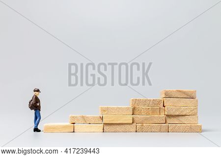 Miniature People Traveller Standing On Wooden Block On Gray Background
