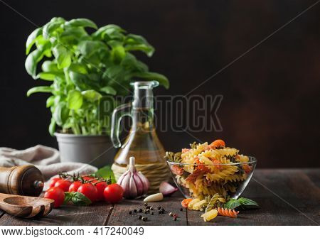 Raw Tricolor Fusilli Pasta In Glass Bowl With Oil And Garlic, Basil Plant And Tomatoes On Wooden Bac