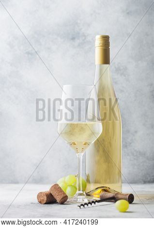 Glass And Bottle Of White Wine With Grapes And Corkscrew On Light Table Background.