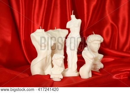 Collection Of Beautiful Sculptural Candles On Red Satin