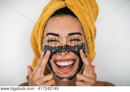 Young Smiling Woman Applying Charcoal Mask On Face - Happy Girl Having Skin Care Spa Day At Home - H