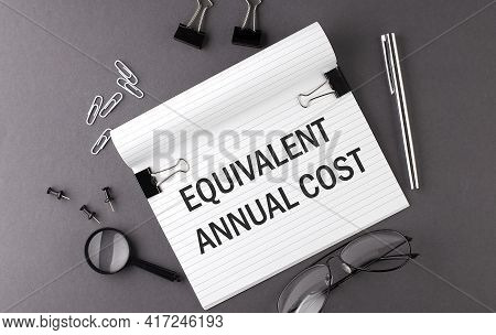 Text Equivalent Annual Cost On Notebook And Office Tools On The Gray Desktop
