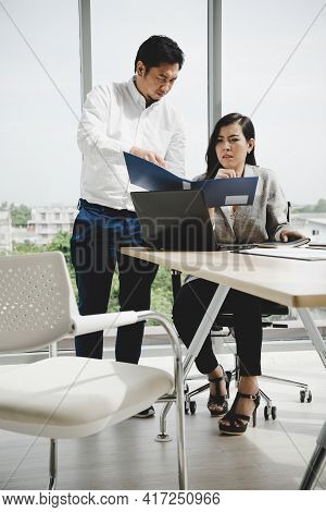 Asian Manager Holding And Pointing File To Ask Question Sale Woman Summary Report In Meeting Room
