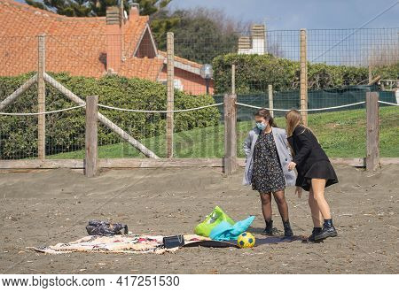 Two Masked Young Women On The Beach In Winter During The Wave Of Pandemic (covid 19) In Marina Di Sa
