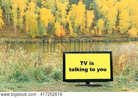 The Tv Speaks To You Is Written On The Tv Screen Which Is Installed On The River Bank In The Autumn.