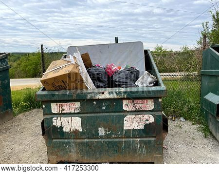 Burke County, Ga Usa - 04 15 21: A Green Rusted Waste Dumpster At A County Dump Overflowing Mattress