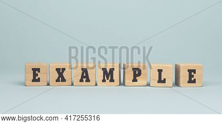 The Word Example Made From Wooden Cubes On Blue Background. Conceptual Photo