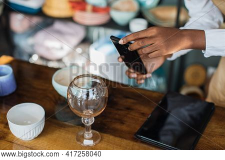 Close Up Of Black Saleswoman Using Modern Smartphone For Taking Photo Of Shiny Glass At Store. Worke