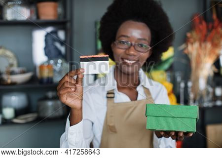 Smiling Afro American Saleswoman Holding Paper Box And Credit Card While Standing At Decor Store. Co