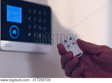 Man Arming Or Disarming Home Security Alarm.