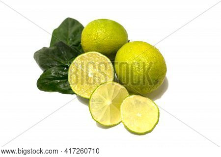 Fresh Lime Fruit. Whole Fruits And Cut. Lime Leaves. Studio Photography On A White Background.