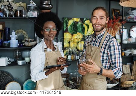 Beautiful Black Saleswoman Typing On Digital Tablet While Caucasian Bearded Seller Holding Glass Cup