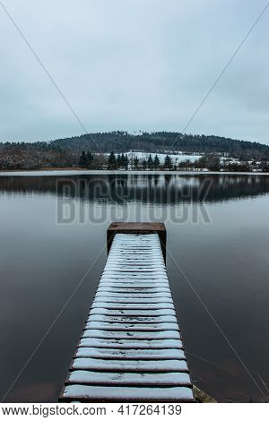 Wooden Empty Pier On Lake Covered With Fresh Snow. Winter Pond With Small Jetty And Snow. Foggy Lake