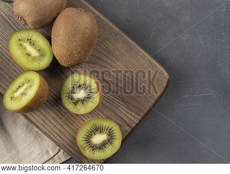 Half Of Ripe Kiwi Fruit On The Wooden Desk Preparing For Cooking Or Eating. Healthy Snack Of Kiwi Fr