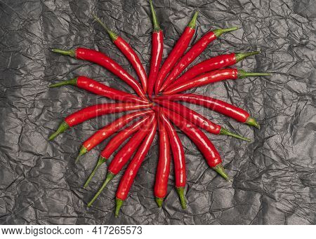 Round Pattern Of Red Hot Chili Peppers In A Black Backdrop. Abstract Image Of Ripe Chili Peppers