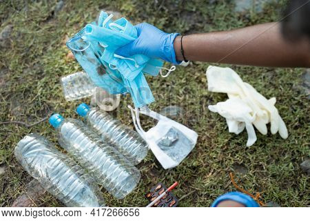 Shoulder Shot Of Volunteer Or Trash Collector Collecting Medical And Other Plastic Waste From Street