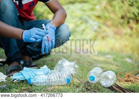 Unrecognizable Volunteer Or Waste Collector Busy Sepereating And Collecting Discarded Medical Or Ppe