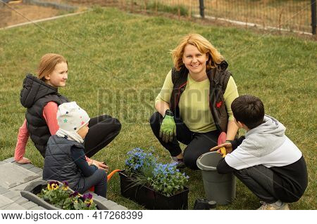 Mother With Many Children Plants Flowers In Pots In Front Or Back Yard Of House. Happy To Spend Time